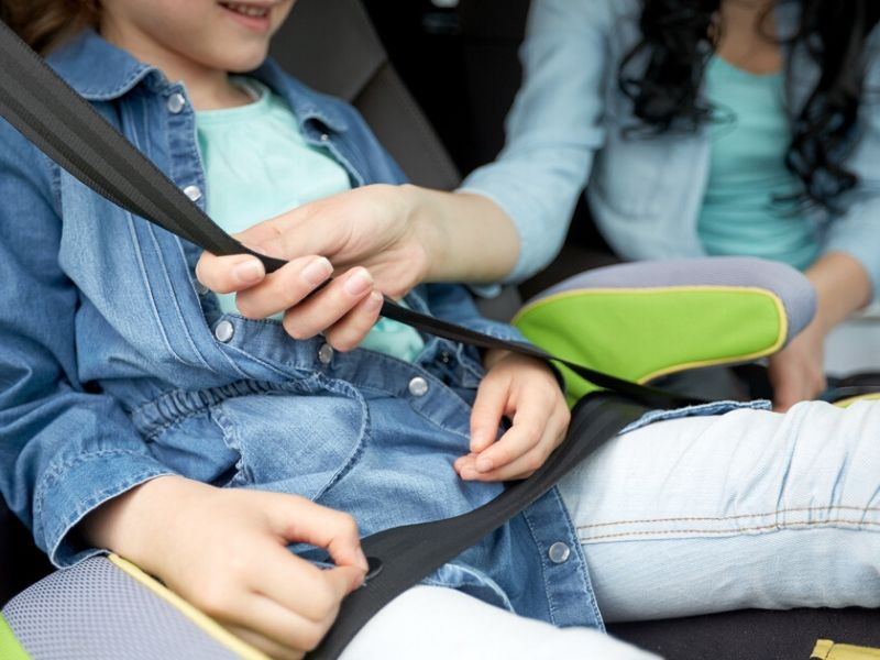child in car with seat belt