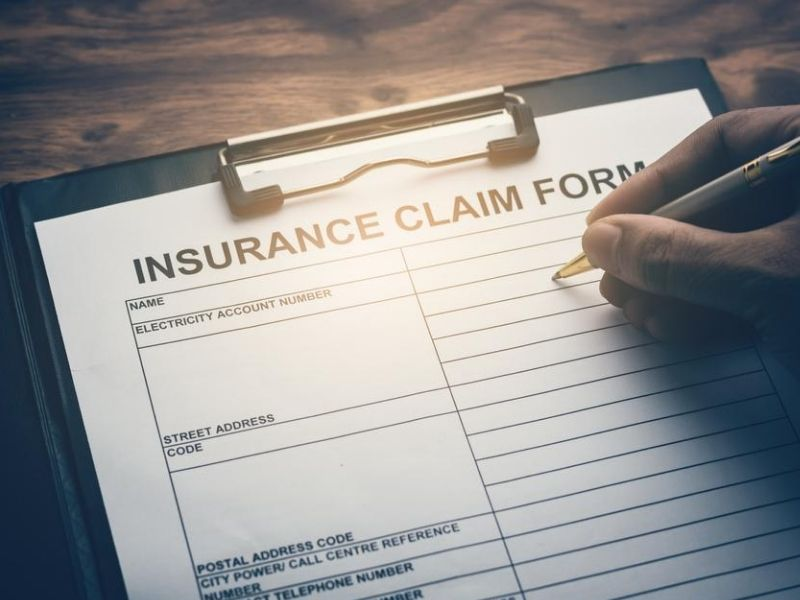 person filling up insurance claim form